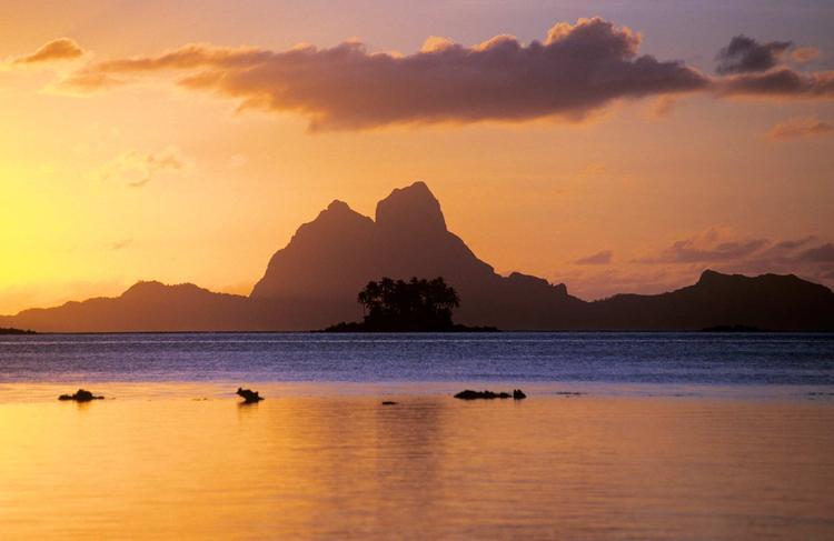 Coucher de soleil, avec au loin, la silhouette caractéristique de l'île de Bora Bora ©P. Bacchet