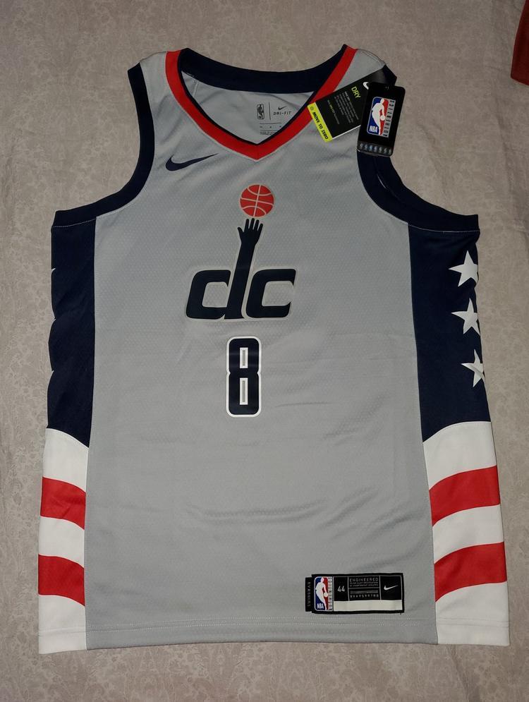 Chemise grise de Washington Wizards sur une table.  Il porte le numéro 8, le logo DC sur la poitrine et des détails du drapeau des États-Unis sur les côtés.