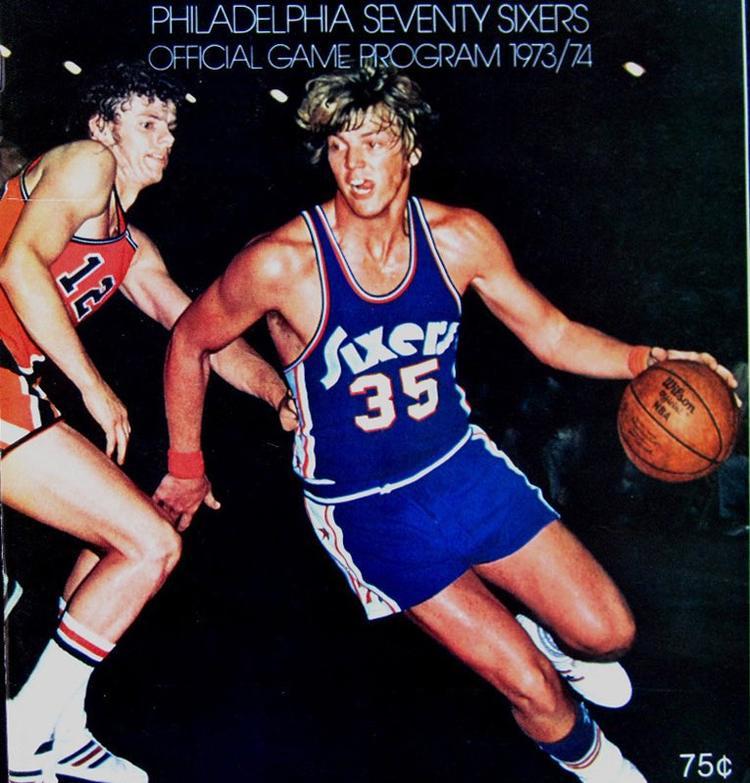 Capa do guia da temporada 1973-74 do Philadelphia 76ers. Um jogador com uniforme azul está driblando um adversário.