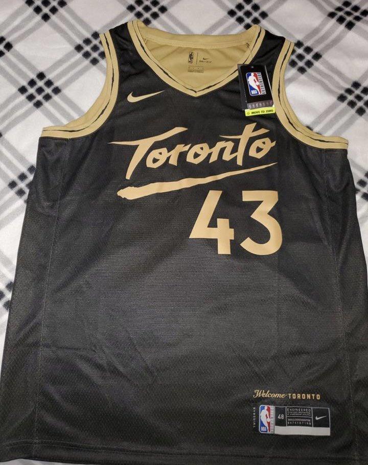 Chemise noire des Toronto Raptors.  Elle est sur une table.  Le nom Toronto et le nombre 43 sont en or.